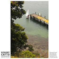 A man sailing a dinghy holds the wharf at Somes Island, Wellington, New Zealand.<br />