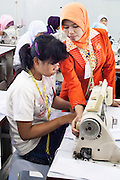 An instructor at the Development Center for Human Resources and Product Industry Enterprises or (Balai Pengembangan SDM & Produk IKM), demonstrate how to operate a sewing machine to a student.  Semarang, Indonesia.  May 14, 2013.