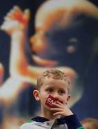 Joshua Florez, 4, puts a campaign sticker over his mouth as Republican presidential candidate Carly Fiorina speaks Wednesday, Jan. 20, 2016, at a right to life campaign stop at the Greater Des Moines Botanical Garden.