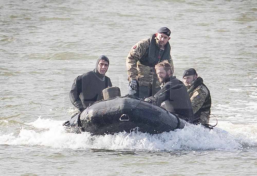 © Licensed to London News Pictures. 12/02/2018. London, UK. Members of the Royal Navy Bomb Disposal Team ride in a boat near the location of the unexploded bomb next to London City Airport which remains closed. A World War II era bomb was found in The River Thames during routine work on nearby King V Dock. Police have evacuated nearby residents, closed the airport and set up a 214-metre exclusion zone. Photo credit: Peter Macdiarmid/LNP