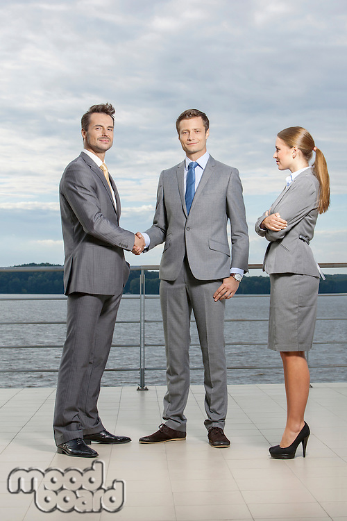 Full length portrait of young businessmen shaking hands while businesswoman looking at them on terrace