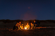 Friends play guitar around a campfire on South Beach, near Newport Oregon.