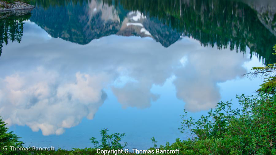 Cumulus clouds formed over the mountains to the east.  The reflection in Watson Lake was dynamic and every changing.  The clouds were framed by the vegegation on the near shore and the reflection of vegetation and mountains on the top.