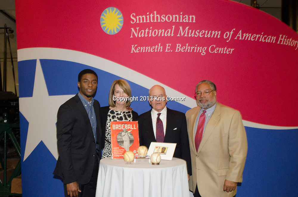 """WASHINGTON, DC - APRIL 15:  Chadwick Boseman, Carol Melton, Executive Vice President for Global Public Policy of Time Warner Inc,  John Gray, Director of the Smithsonian Museum of American History, and Lonnie G. Bunch III,  director of the Smithsonian's National Museum of African American History and Culture  pose with Jackie Robinson artifacts during the Washington DC screening of Warner Bro's film """"42"""" at Smithsonian Museum of American History on April 15th, 2013. Guests included star of the film Chadwick Boseman, John Gray, Carol Melton, and Lonnie Bunch. Photo by Kris Connor/Warner Bros"""