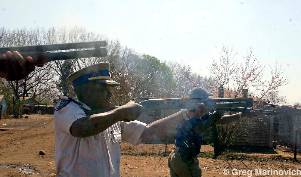 Superintendent Tshepo Chocho, head of the Johannesburg's Metro Police special riot unit (centre) opens fire with rubber bullets as residents of the informal settlement of Zone 1, Protea South battle with police in a protest against poor service delivery in the fields of water, electricity, housing,sanitation and health, Sept 1 2007.  Informal settlementsthat dot the Sebokeng/Evation area south of Johannesburg have been taking to the streets to protest lack of service delivery, or inadequate services that are not what they believe were promised them by the African National Congress before they came into power in 1994.  Photo Greg Marinovich