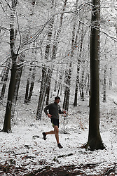 © Licensed to London News Pictures. 27/12/2017. Leith Hill, UK. A runner jogs through the snow covered forest on Leith Hill in the Surrey Hills. Photo credit: Peter Macdiarmid/LNP