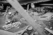 An old man sitting next to his familys grave in the center of Balakot - he lost five of his  children during the quake, all buried in the same grave.<br /> Balakot  - nov. 6 2005.