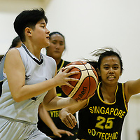 Debbie Ngo (#12) of Singapore Institute of Management drives against (#25) of Singapore Polytechnic. (Photo © Lim Yong Teck/Red Sports)