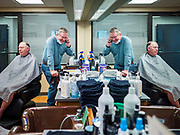 15 MAY 2020 - DES MOINES, IOWA: BRUCE FULTON, a barber at Ferg's Barbershop in downtown Des Moines, makes a reservation while a client waits for his haircut to be finished. The barbershop opened Friday for the first time in two months and by midday was completely booked through next week. The Governor of Iowa allowed most businesses in Iowa to reopen today, including restaurants, barbershops, coffee shops and malls. Restaurants are supposed to be working at 50% of normal capacity and barbershops are urged to take reservations and not allow customers to wait in the shop.  Movie theaters, bars, museums, zoos, and casinons are still closed. On Friday, 15 May, Iowa reported 14,049 cases of COVID-19 and 336 deaths from disease since the start of the pandemic. Iowa's total number of infections continue to rise and several communities in Iowa have emerged as national hotspots for the spread of Coronavirus (SARS-CoV-2).        PHOTO BY JACK KURTZ