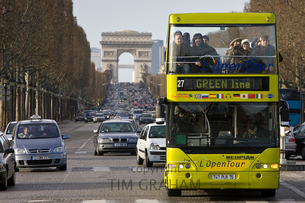 Tourist bus among traffic on Champs-Élysées in front of the Arc de Triomphe, Central Paris, France