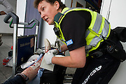 "NHS Paramedic Janet Greenhead attends to a lady passenger in Heathrow airport's terminal 3 who has tripped on escalators and badly gashed her leg. Janet applies a dressing and cleans the deep wound before advising the lady to visit a local hospital. Paramedics 'Responders' are with the cycle response unit (CRU), part of the London Ambulance Service whose job is to attend injuries within Heathrow, cycling through the terminals on mountain bikes. She answers radio calls from those with a cut finger, a baggage handler who's injured an arm, a child who's fallen over with cuts and bruises or a much more serious incident like a cardiac arrest which are common in an airport where passengers feel under stress or who forget to take their medicines while jet lagged. From writer Alain de Botton's book project ""A Week at the Airport: A Heathrow Diary"" (2009). ."