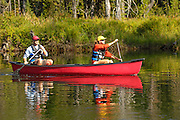 USA. Idaho, McCall. Couple canoeing on the North Fork of the Payette River. MR