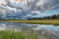 Storm clouds reflected in still waters of Snake River at Schwabacher Landing Grand Teton National Park Wyoming