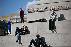 FEB 26 2014 Tourists get a sunbath at Trafalgar Square.