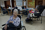 Israeli elderly woman Tzabrika,88,  (right) sits among other patients  at the Haderim Nursing home in Kibbutz Na'an in central Israel. She is one of the more than 10,000 Israeli patients issued a license to take medical marijuana by the Ministry of Health . She is  suffering from Parkinson's Disease and Dementia and the medical staff at the nursing home claim that she is less spastic and is able to eat better since she started to take the drug...Researchers in israeli claim that cannabis can not only help bring relief to cancer patients in  pain ,  lower high blood pressure,improve appetite , to even helping with the recovery from a heart attack or post traumatic stress disorder ...Tikun Olam developed a new strain from cross breeding which has removed nearly all the THC (tetrahydrocannabinol) which is what makes one feel stoned or high. This new strain has a high concentration level of cannabidiol (CBD) which has  anti-inflammatory and anti-anxiety agents. This new strain is attractive to patients who  old or are children or work and sensitive to THC...The company produces not only the flowers and ready rolled cannabis cigarettes but also cannabis-laced chocolates, cookies, honey, toffee, ointments, gum and cakes ...Marijuana is illegal in Israel but there are over 10,000 Israelis taking medical marijuana to treat a range of illnesses from Cancer, Parkinson's disease to post traumatic stress disorder .(Photo by Heidi Levine/Sipa Press).