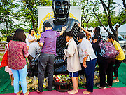 01 JANUARY 2016 - BANGKOK, THAILAND:          People rub a statue of the Buddha for luck during the annual New Year's mass merit making ceremony on at Sanam Luang in Bangkok. The ceremony is sponsored by the Bangkok city government. More than 500 Buddhist monks participated in the ceremony this year. Thais usually go to temples and religious observances to meditate and make merit on New Year's Day.    PHOTO BY JACK KURTZ