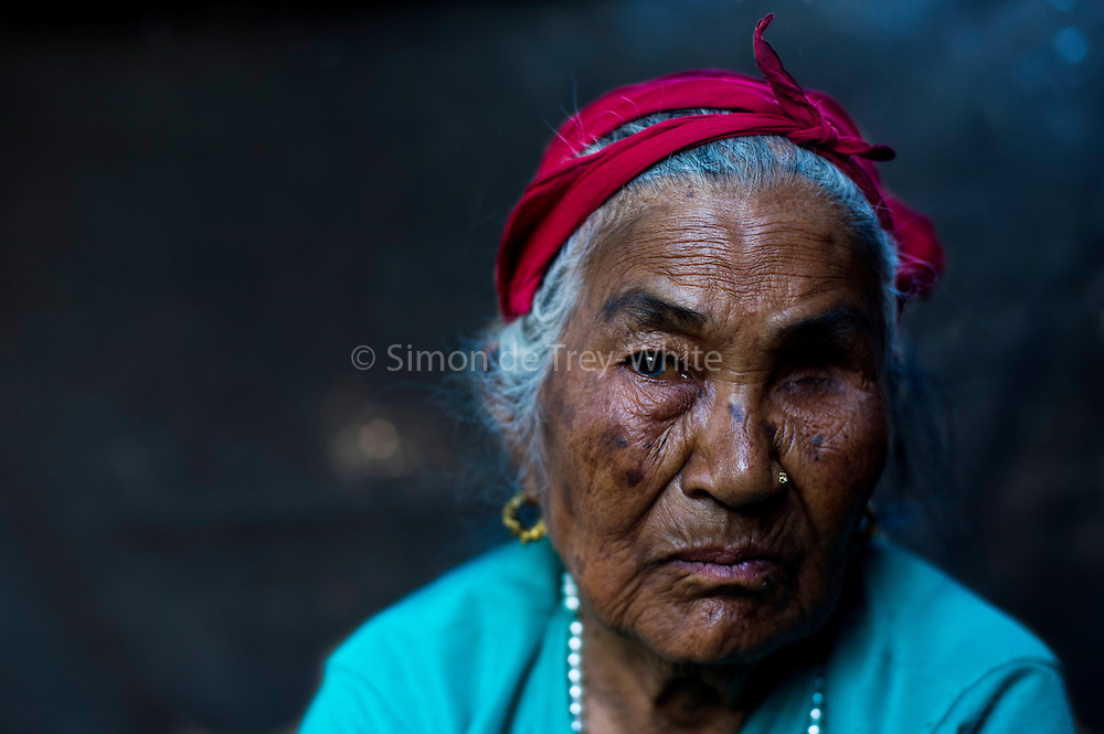 6th May 2015, Kathmandu, Nepal.  Ruku Khattri Chhetri (89) in Ramkot village, near Kathmandu, on the 6th May 2015.<br /> <br /> This mother of 7 lived through the last major earthquake to hit Nepal 81 years ago in 1934. She remembers it clearly, she was 8 years old at that time and was carrying her little 3 year old brother outside in the fields. When the earthquake struck she kneeled down and shielded him to protect him, the ground and nearby buildings shook violently  she saw a cloud of dust rise 'like fog in winter'  from nearby Bimdungar village caused by all the falling buildings, it happened very fast and many people died. She stayed where she was until her grandfather came and found them - as her parents were not available. Her father had jumped from the second story of their house during the earthquake to save himself and broken his leg.<br /> <br /> During the 2015 earthquake she was outside her house and fell to the ground when the earth shook, she found herself covered in dust from her house that had collapsed behind her , she crawled away crying for help and was soon rescued by neighbours. When asked about the future she said  &lsquo;I fear more suffering is to come since I am still alive&rsquo; .&lsquo;If another earthquake comes I want to die fast, I don&rsquo;t want to be injured&rsquo;. She lost one eye to cancer and is all but blind in the other. <br />  <br /> An earthquake with magnitude 7.8 occurred near Lamjung, Nepal, 50 miles northeast of the capital Kathmandu at 06:11:26 UTC on Apr 25, 2015. The capital has seen considerable devastation including the nine-story Dharahara Tower, one of Kathmandu's landmarks built by Nepal's royal rulers as a watchtower in the 1800s and a UNESCO-recognised historical monument. It was reduced to rubble and there were reports of people trapped. Portions of historic buildings in the World Heritage gazetted site of Patan have also been destroyed as well as many buildings in the old city. <br /> <br /> PHOTOGRAPH BY AND COPYRIGHT OF SIMON DE TREY-WHITE<br /> <br /> + 91 98103 99809<br /> e