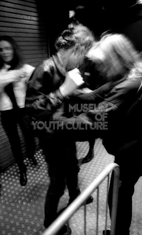 A female member of security searches a woman on the main door of the Hacienda, Manchester, early 1990's