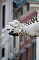 Milan, Italy, Duomo Cathedral - stone dog gargoyle with street buildings in the background.