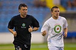 PODGORICA, MONTENEGRO - Wednesday, August 12, 2009: Wales' assistant coach Dean Saunders and Neal Eardley warm-up wearing a shirt in support of former captain John Hartson who is battling against cancer, and to promote awareness of men's health issues with web site checkemlads.com, before an international friendly match against Montenegro at the Gradski Stadion. (Photo by David Rawcliffe/Propaganda)