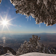 Bright sunshine brings out the icicles and melting snow atop the Sandia Crest overlooking the city of Albuquerque, New Mexico.