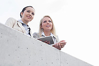 Low angle view of young businesswomen with digital tablet looking away while standing on terrace against sky