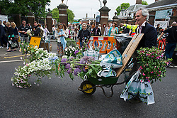 © London News Pictures. 23/05/2015. London, UK. A man carrying his purchase in a wheelbarrow. Members of the public carry exhibitors' plants from the 2015 Chelsea Flower show, which ends today (Sat). The Royal Horticultural Society flagship flower show has been held at the Royal Hospital in Chelsea since 1913. Photo credit: Ben Cawthra/LNP
