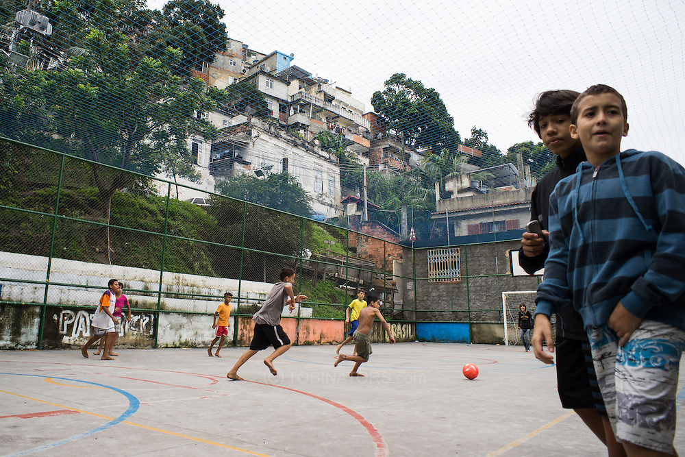 Children play football on a small concrete pitch in the Santo Amaro favela, Rio de Janeiro, Brazil. The favela has not been pacified and is one of the less well known of Rio's favelas. A heavily armed police presence was inevidence and there was no trouble of any sort while we were there. According to our guide, Patrick Ashcroft, a teacher and research worker who lives in the favela, violence is rare in this favela. Photo by Andrew Tobin/Tobinators Ltd
