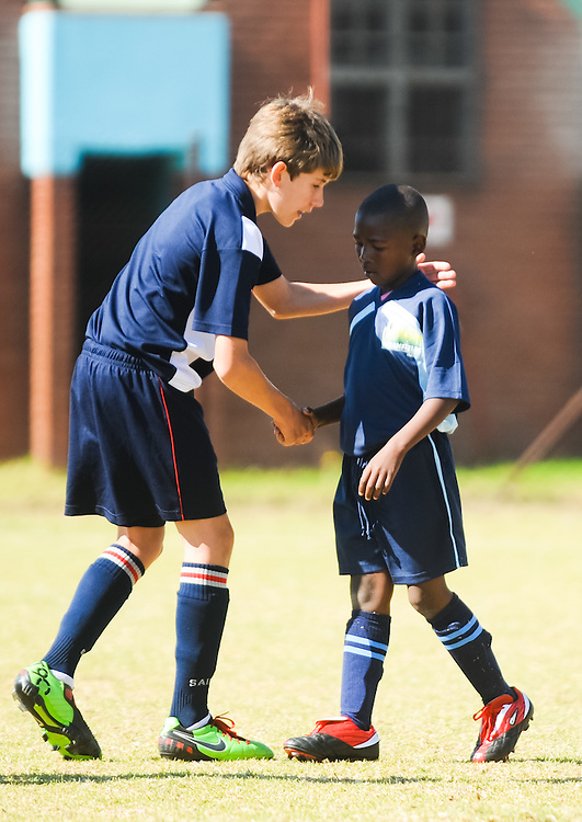 A St. Stithians College Prep player, left, and Ebony Park Primary player shake hands after their friendly match Tuesday, June 8, 2010 during a Dreamfields Project event in the Ivory Park township of Johannesburg, South Africa. St. Stithians students raised money to buy complete soccer uniforms for Ebony Park and another team through the Dreamfields Project. The Dreamfields Project is a non-profit organization that aims to put resources for playing soccer into townships and rural areas in South Africa. Photo by Bahram Mark Sobhani