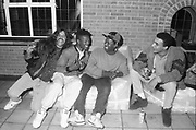 Group of guys on sofa outside, UK, 1980s.