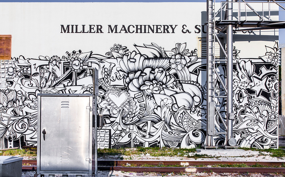 An elaborate, almost psychedelic, black and white mural sprawls over an industrial building adjoining the Florida East Coast Railway tracks in Miami's Wynwood neighborhood