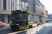 blue tram number 77 on the linia czasowa to krowodrza passes through krakow old town on sunny afternoon in september 2005. adverts on the tram read panorama firm in yellow writing.