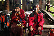 A Tibetan Buddhist nun and a monk rest out of the rain at a teahouse during a pilgrimage to Shenpu, Buddha's Tears waterfall.