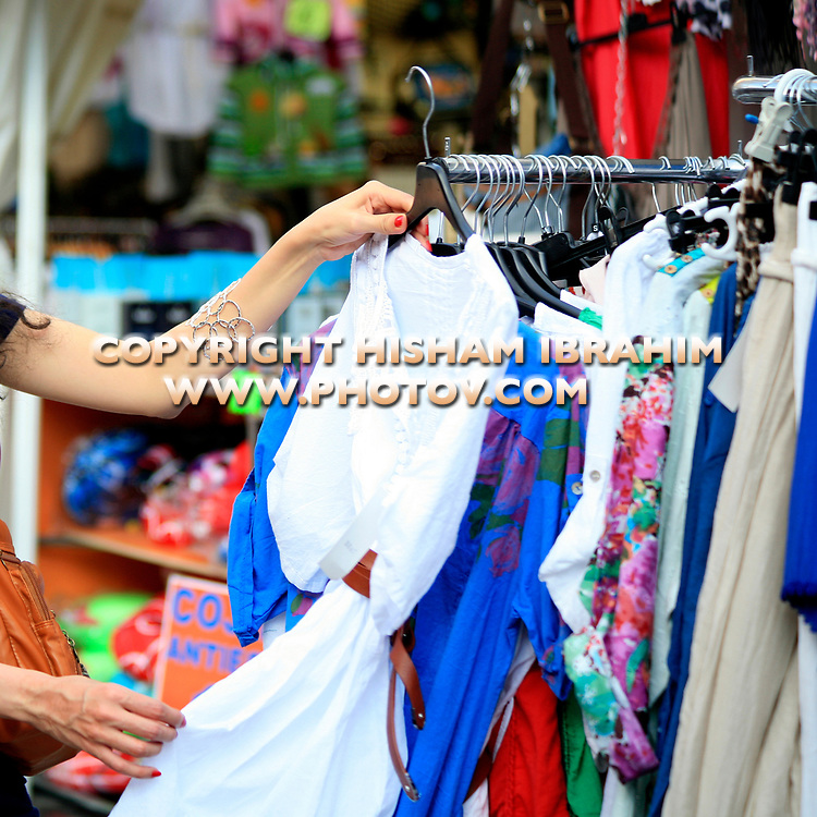 Woman shopping for clothing at 'El Rastro' Flea Market, Madrid's famous Flea Market located in the 'La Latina District' - Madrid, Spain.
