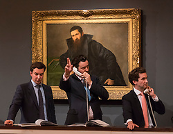 "© Licensed to London News Pictures. 07/12/2016. London, UK. Sotheby's staff make bids on behalf of telephone clients in front of ""Portrait of an architect"" by Lorenzo Lotto which sold for a hammer price of GBP340k (est. GBP 200-300k), at the Old Masters Evening Sale at Sotheby's in New Bond Street. Photo credit : Stephen Chung/LNP"