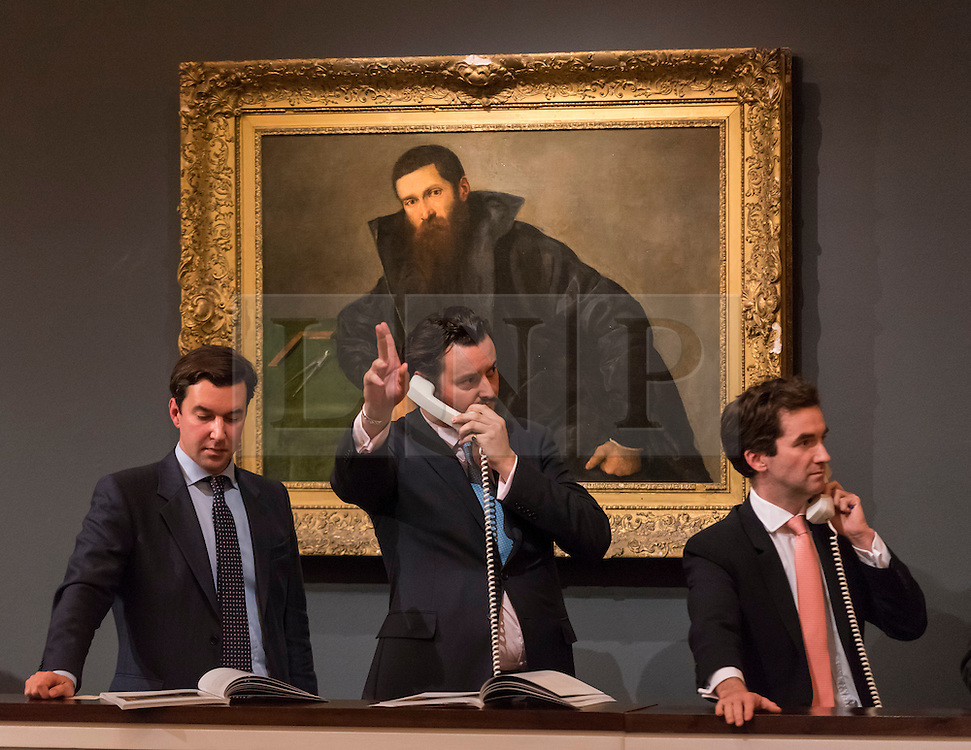 """© Licensed to London News Pictures. 07/12/2016. London, UK. Sotheby's staff make bids on behalf of telephone clients in front of """"Portrait of an architect"""" by Lorenzo Lotto which sold for a hammer price of GBP340k (est. GBP 200-300k), at the Old Masters Evening Sale at Sotheby's in New Bond Street. Photo credit : Stephen Chung/LNP"""