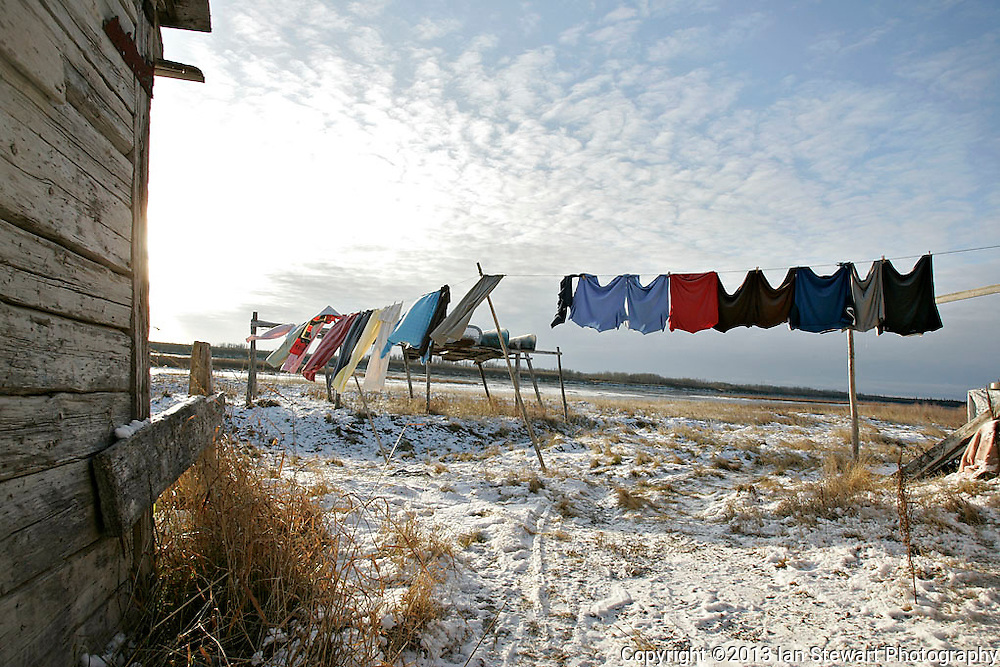 Laundry dries in a backyard with riverboats and the Attawapiskat River in the distance. <br /> <br /> (Ian Stewart photo)