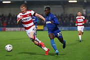 AFC Wimbledon defender Paul Osew (37) taking on Doncaster Rovers defender Brad Halliday (2) during the The FA Cup match between AFC Wimbledon and Doncaster Rovers at the Cherry Red Records Stadium, Kingston, England on 9 November 2019.