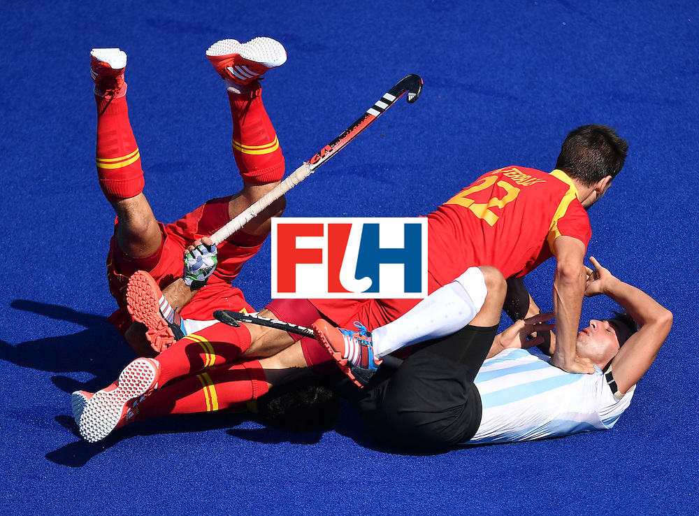 TOPSHOT - Spain's Manel Terraza (R top) falls over Argentina's Matias Paredes (R bottom) during the men's quarterfinal field hockey Spain vs Argentina match of the Rio 2016 Olympics Games at the Olympic Hockey Centre in Rio de Janeiro on August 14, 2016. / AFP / MANAN VATSYAYANA        (Photo credit should read MANAN VATSYAYANA/AFP/Getty Images)