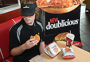 This handout photo from KFC shows a McDonald's employee eating KFC's new Doublicious sandwich  Monday, July 12, 2010 in Louisville, Ky. (Photo by Brian Bohannon).
