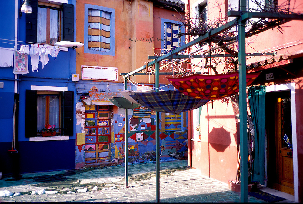 Colorfully-painted house front on Burano, Venice.  Laundry hanging in front of one house; umbrellas hanging open and upside down from  a wooden framework in front of another house.  Main colors blue, red, orange.