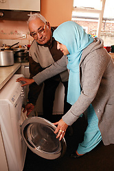 Asian carer with elderly Asian man using the washing machine in the kitchen, ***NOT TO BE USED IN THE EAST MIDLANDS***