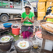 A woman cooks street food at the fish and flower market in Mandalay, Myanmar (Burma).