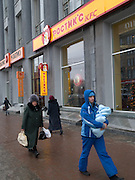 Nowosibirsk/Russische Foederation, RUS, 19.11.07: Passanten vor der Kentucky Fried Chicken (KFC) Filiale im Zentrum der sibirischen Hauptstadt Nowosibirsk. Ein Mann traegt sein Kind im Arm.<br /> <br /> Novosibirsk/Russian Federation, RUS, 19.11.07: Passersby in front of the Kentucky Fried Chicken (KFC) chain store in the Sibirian capitol Novosibirsk.  Man is carrying a child in his arms.
