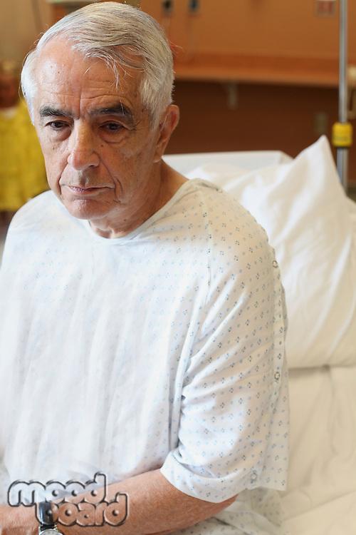 Elderly man sitting on hospital bed