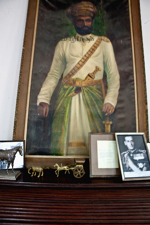 Portrait of a previous maharajah, of Mountbatten, and figurines of elephant, horse, etc., on display at a maharajah's palace.