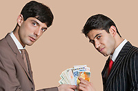 Portrait of young businessmen showing Euros over colored background