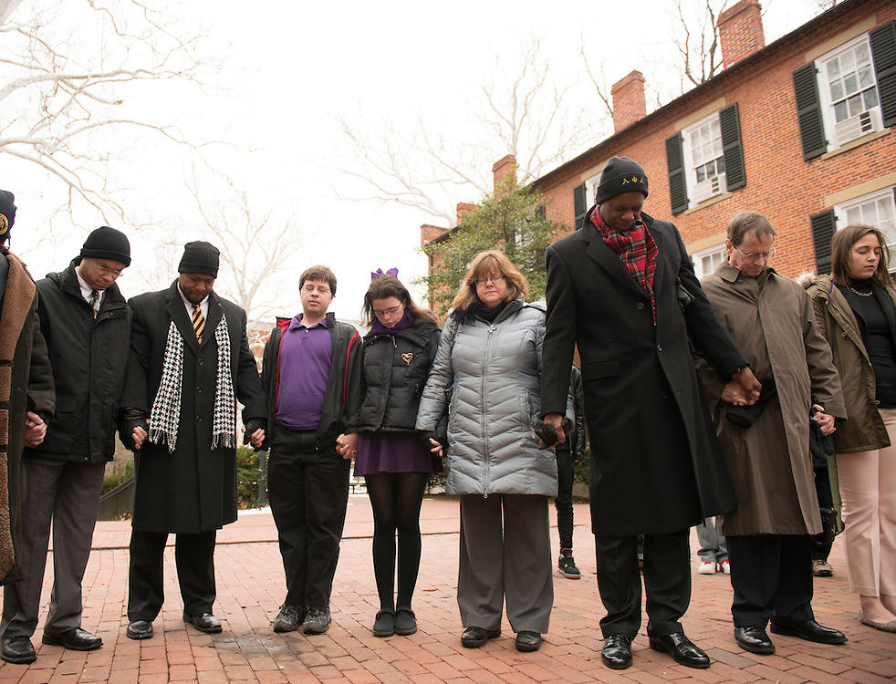 Ohio University students and faculty hold hands and listen to prayer before beginning a silent march held in remembrance of Martin Luther King. (Photo by Olivia Wallace)