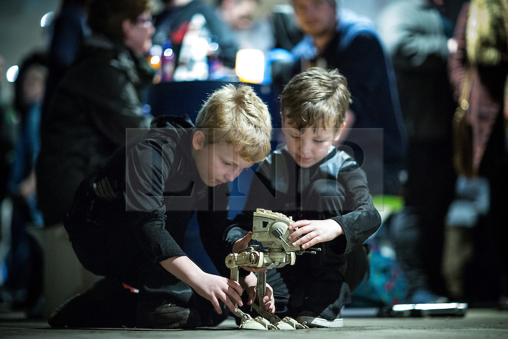 """© Licensed to London News Pictures . 06/12/2015 . Manchester , UK . Boys playing with an AT-ST in the cantina . Fans attend Star Wars exhibition """" For the Love of the Force """" at Bowlers Exhibition Centre in Manchester . Photo credit : Joel Goodman/LNP"""
