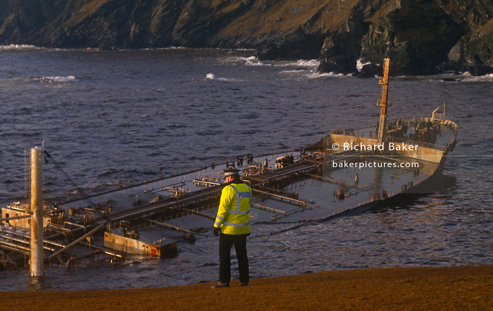 A police officer looks over stormy waves wich crash over the super-structure and funnel of the Liberian-registered MV Braer oil tanker, spilling 84,700 tonnes of crude oil into the North Sea, on 7th January 1993, in Quendale Bay, Shetland, Scotland, UK. It sits below its water-line with crude oil leaking from its ruptured tanks after running ground in hurricane force winds, beaching itself on these rocks in Quendale Bay, west of Sunburgh Head, the Shetland Islands, Scotland. In fast-fading light, this ecological disaster occurred in a beautiful region of Great Britain affecting much native wildlife although the Gulfaks oil the Braer was carrying is lighter therefore more biodegradable and able to disperse better than other North Sea crude.